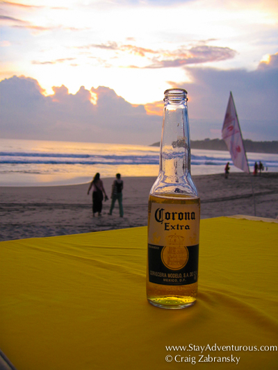 a corona and a sunset in puerto escondido, mexico