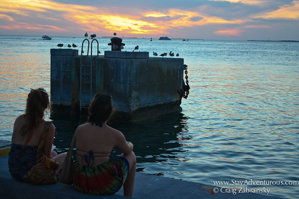 two young women reflect at sunset in mallory square key west