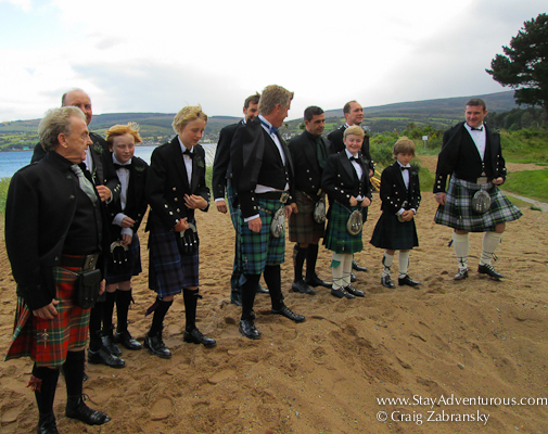 the man in scottish kilts prepare to jump for a photo on the isle of arran in scottland