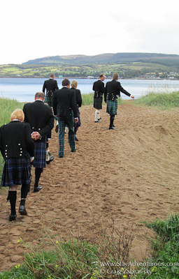 the man in scottish kilts walk to the beach on the isle of arran in scottland