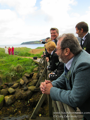 the men in kilts pose on the bridge for wedding photos on the isle of arran