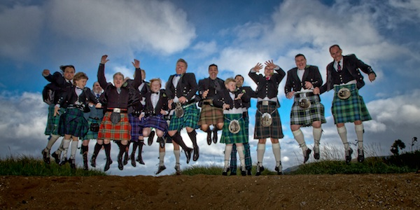the men in scottish kilts jump for a wedding photo on the isle of arran in scottland