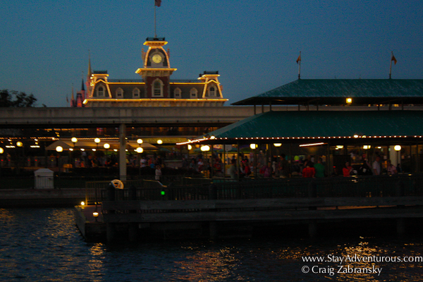 the view of main street and even the cinderella castle from the ferry boat on the water at the magic kindom at night