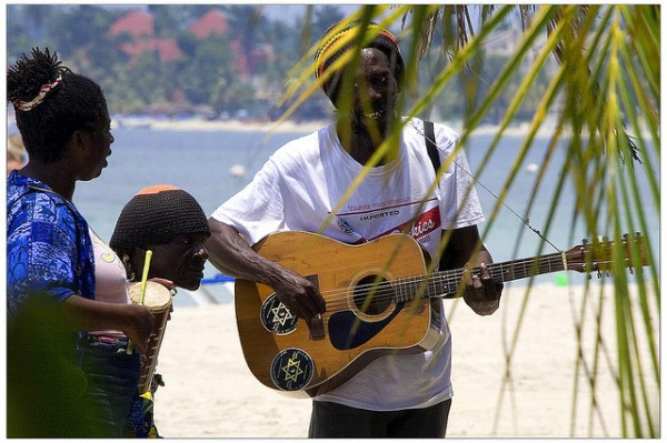 man strumming his guitar on the beach in jamaica