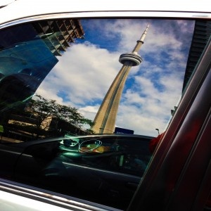 the CN Tower reflected off a car window in downtown Toronto, Ontario, Canada