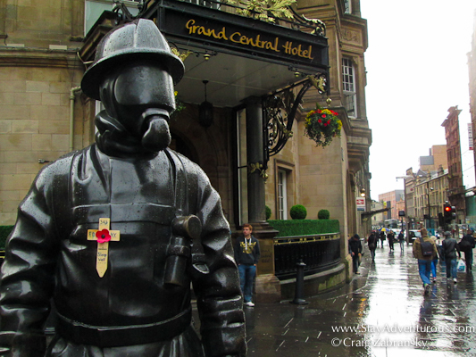fireman monument outside grand central hotel and train staiton in glasgow sctoland decorated to honour September 11th firefighters