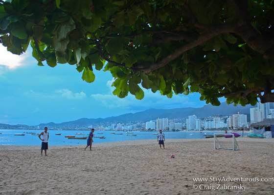 young men about to play soccer (football) on the beaches of Acapulco Bay at sunset in Mexico