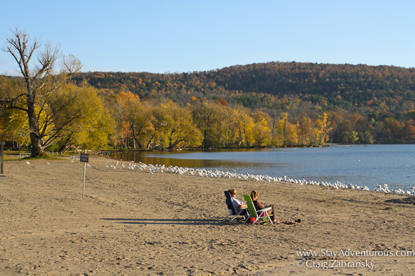 two people lounge at the beachfront in Glimmerglass State Park in Upstate New York