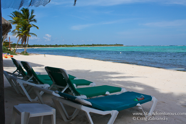 a few lounge chairs on the beach of soliman bay, riviera maya, cancun, mexico