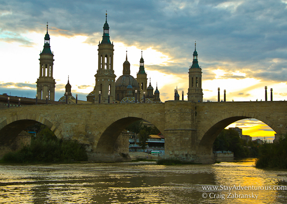 sunset in zaragoza, aragon, spain, with puente de piedra and the basilica del pilar