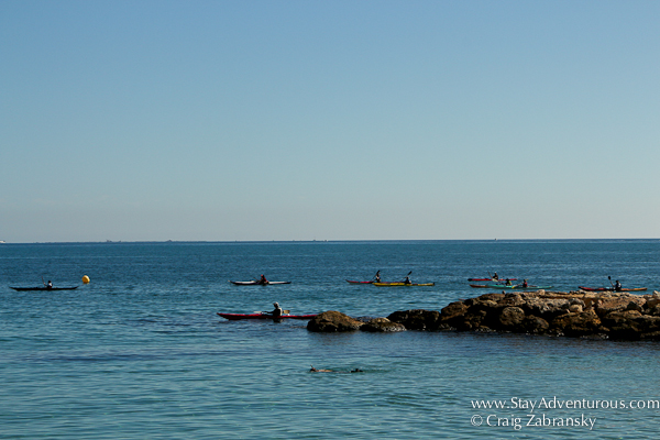 kayak and a snorkeler at the beach in l'ametlla del mar, catalonia, spain