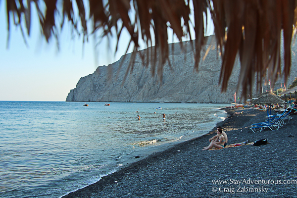 the view from a tiki hut on the black sand beach of Kamari in Santorini, Greece