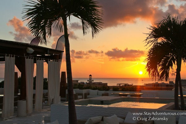 the sunrise in playa del carmen warms the rooftop of the palm at playa