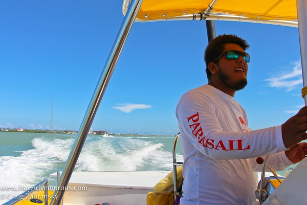 parasail of brekaway cruises captain guides the boat in south padre island, texas