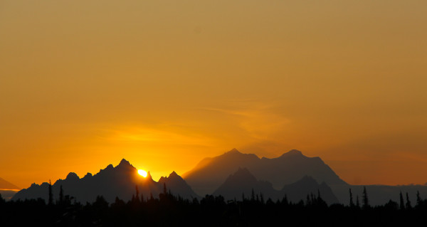 sun hiding behind the Alaskan Mountain Range near Denali in Alaska