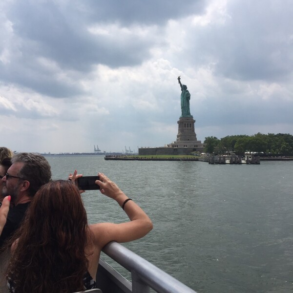 taking a photo of the statue of liberty from the Liberty Cruise part of Top View NYC Tours